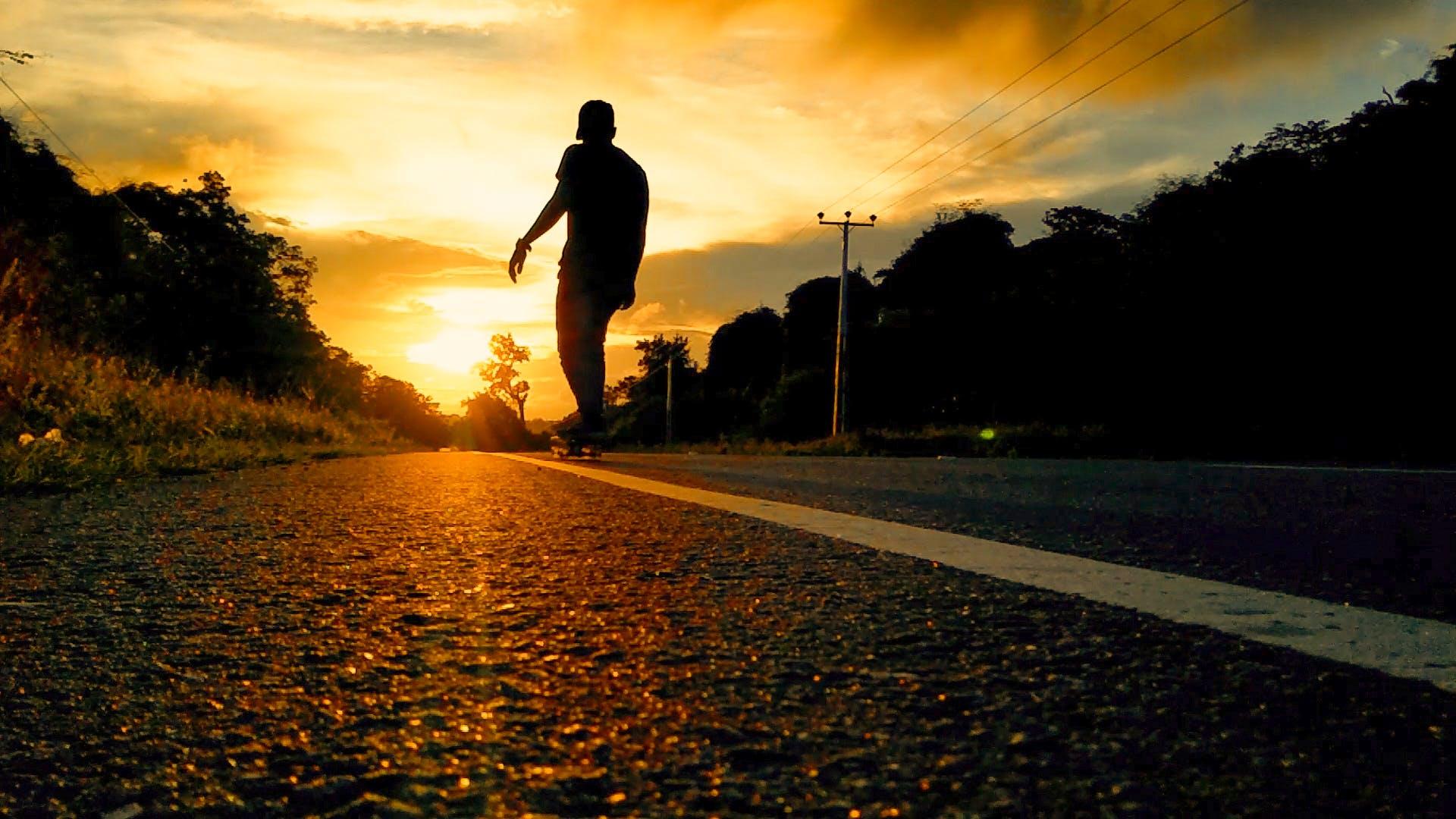Silhouette Photo Of Man Riding Skateboard