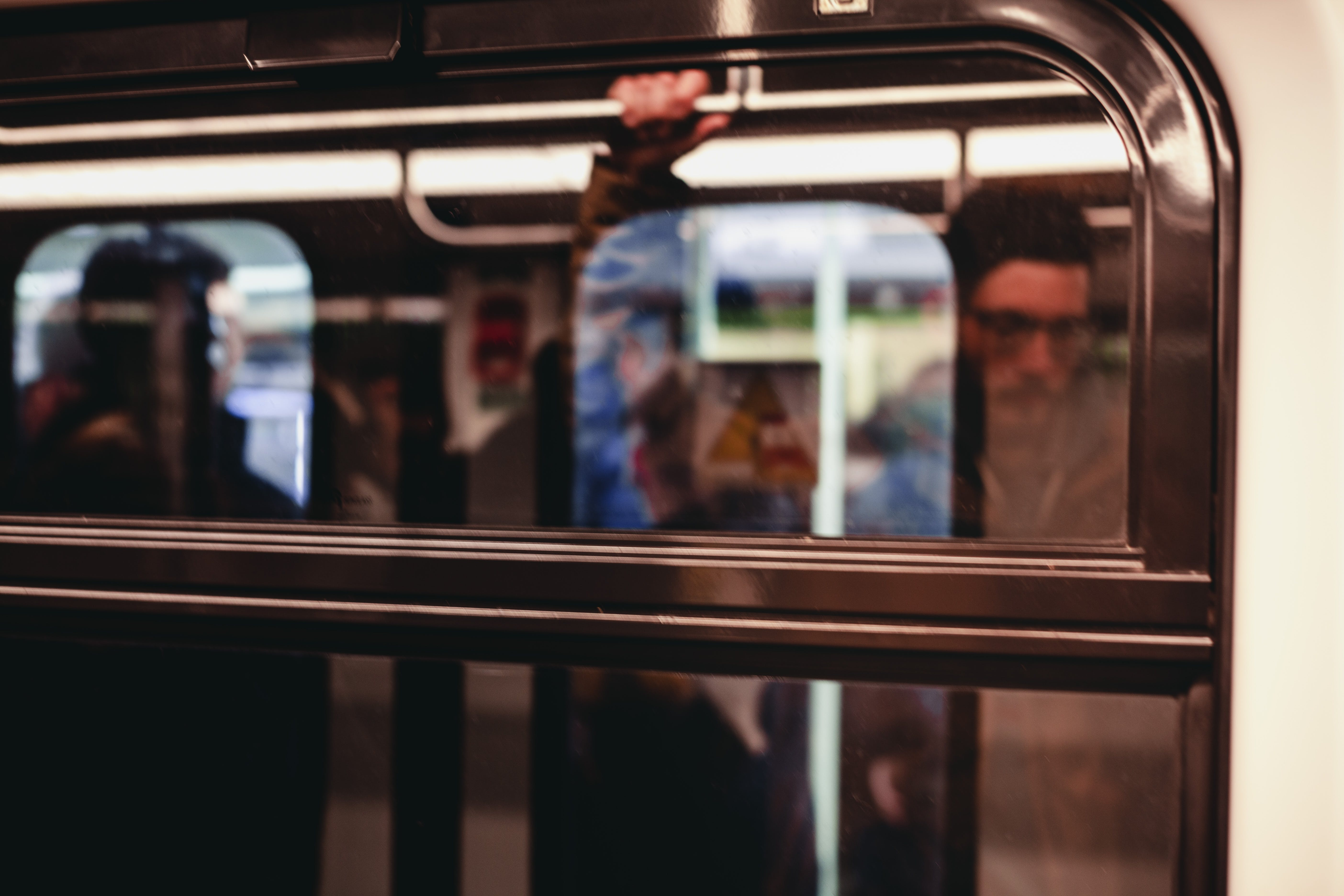Man Standing Inside Train Waiting to Stop
