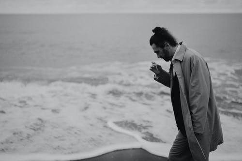A Man Smoking a Cigarette while Walking on a Shore