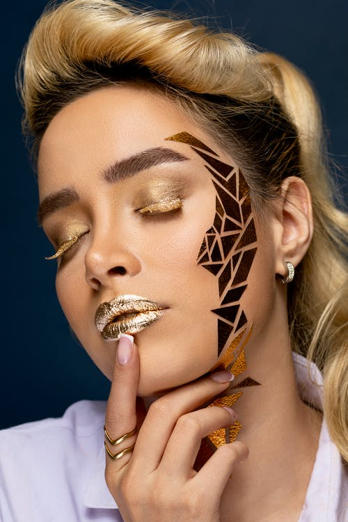 Sensual model with golden makeup touching lips