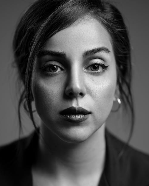 Black and white of serious woman with deep gaze looking at camera on gray background