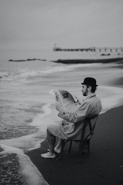 Grayscale Photo of a Man Reading a Newspaper while Sitting on a Chair at the Beach