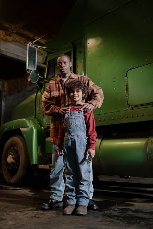 A Father and His Child Standing beside a Green Truck