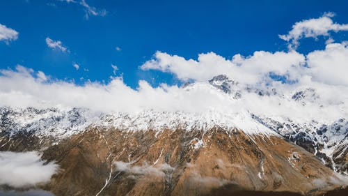 Snow Capped Mountains Under a Blue Cloudy Sky