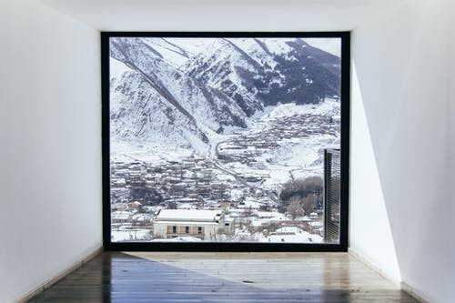 A Window Overlooking a Snow Covered Town