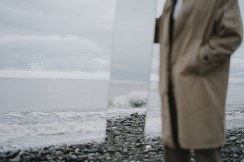 Person Holding Mirror Reflecting Water Waves on Gray Rocky Shore