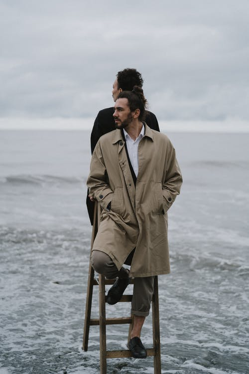 Man in Brown Coat Standing on Beach