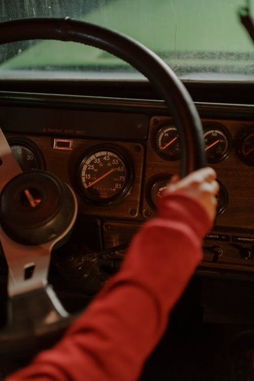 Person in Red Long Sleeve Shirt Driving Car