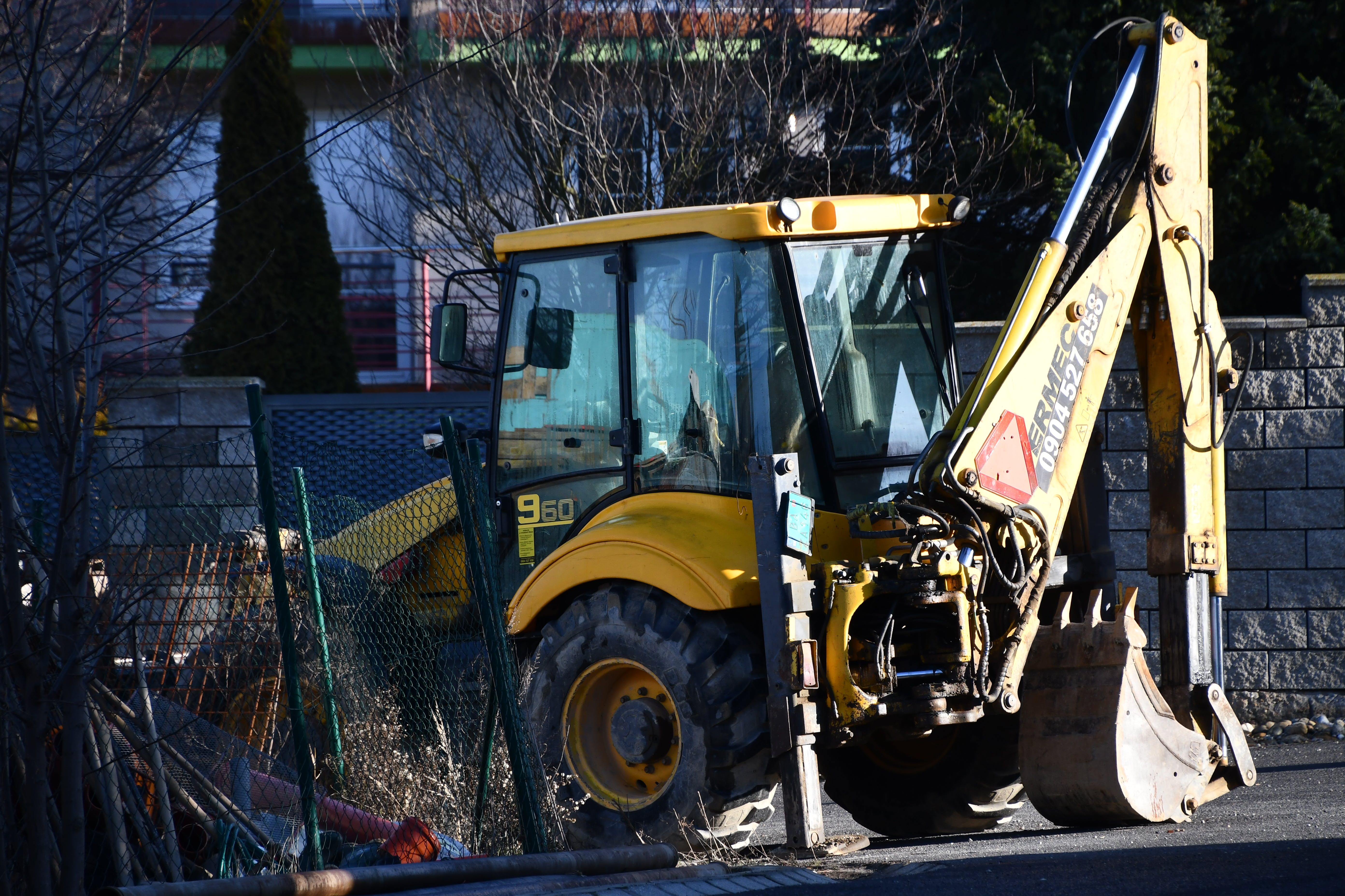 Yellow and Black Backhoe Near the Wire Fence