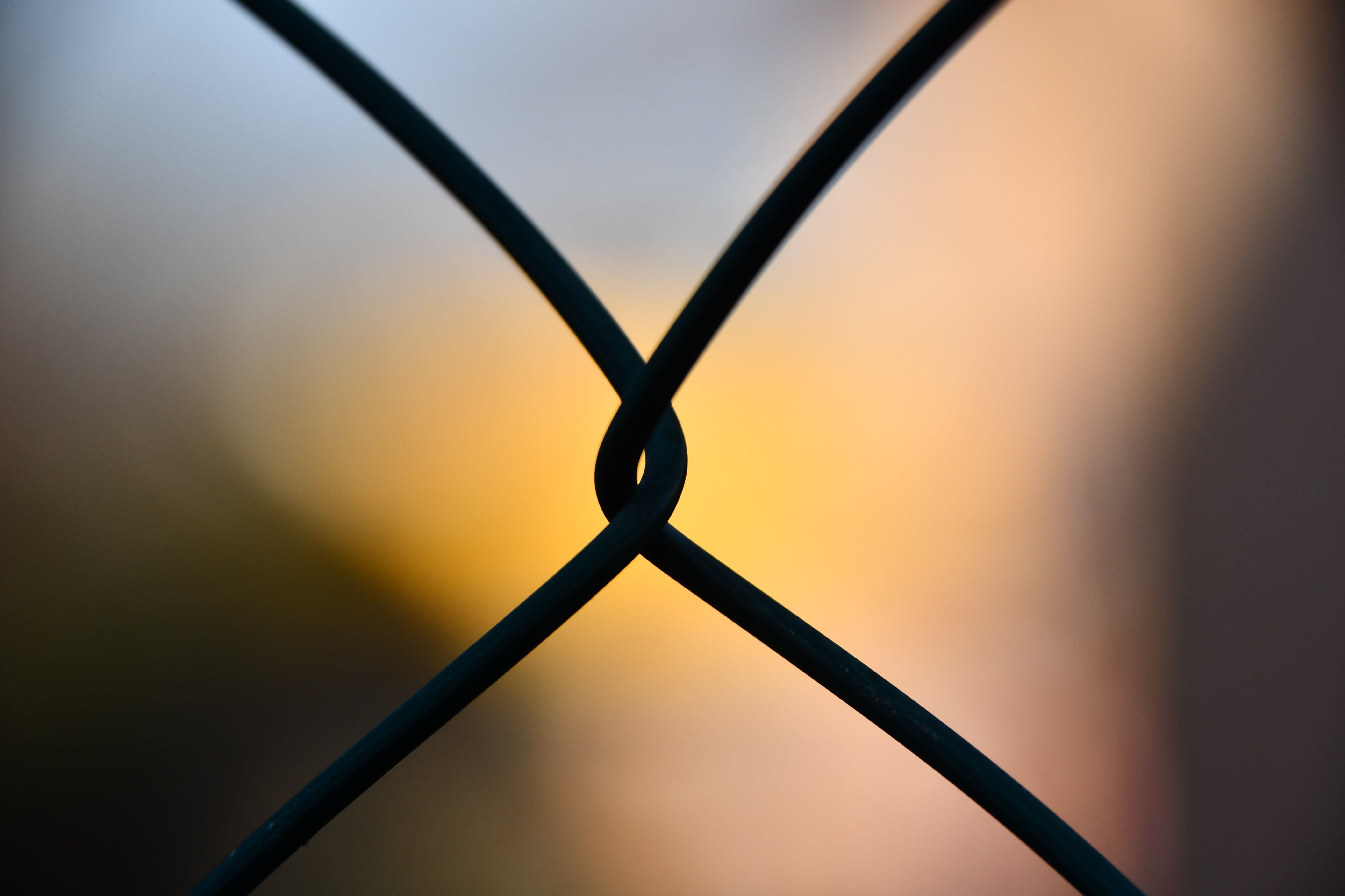 Shallow Focus Photography of Silhouette of Cyclone Wire