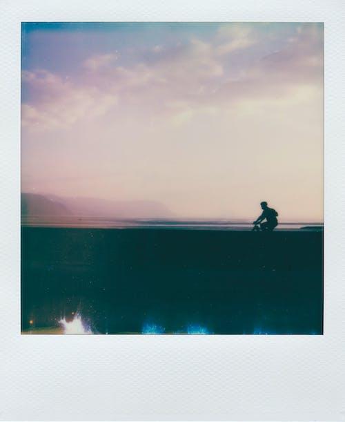 Polaroid Picture of Person Biking Under White Clouds