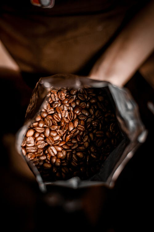 Person with bag full of coffee beans