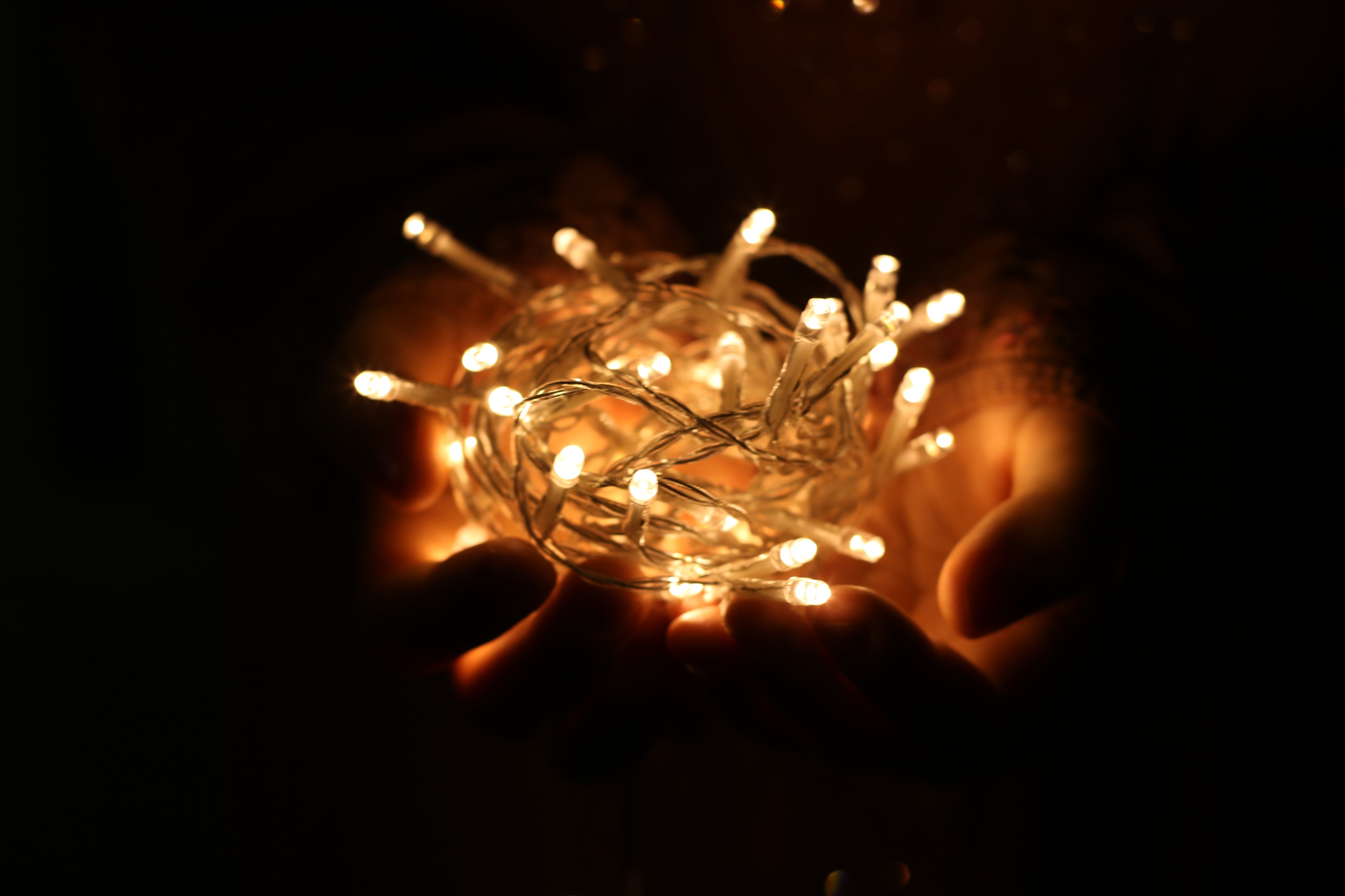 Person Showing White String Lights during Nightime