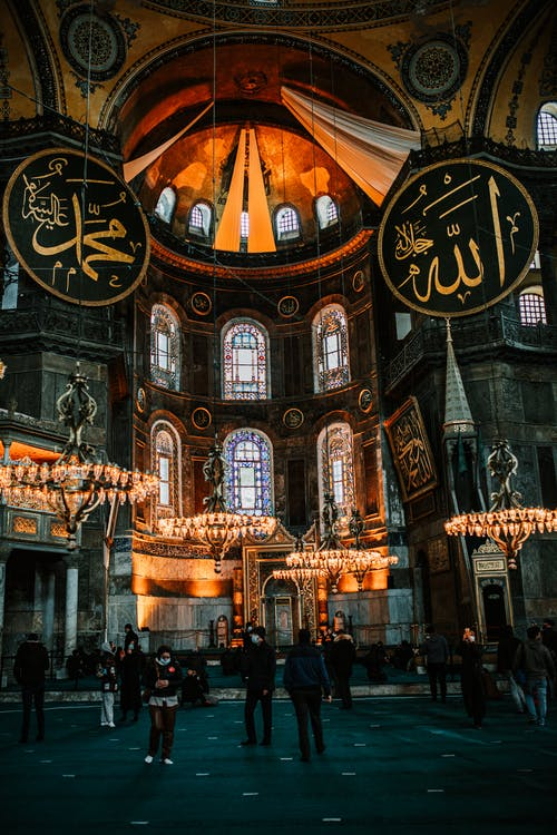 Unrecognizable travelers sightseeing ancient Holy Hagia Sophia Grand Mosque with illuminated chandeliers and Arabic inscriptions on pendants