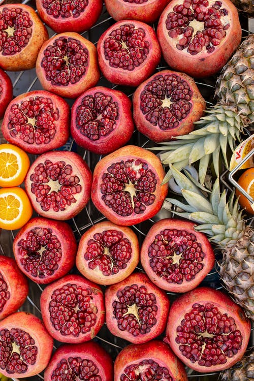 From above of fresh appetizing pomegranates with pineapples and oranges arranged on metal tray in market
