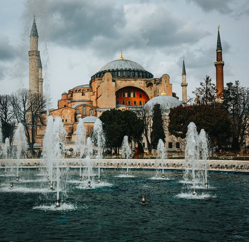 Fountains in square near historic Holy Hagia Sophia Grand Mosque located in Istanbul against overcast sky