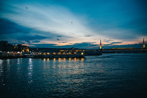 Picturesque scenery of calm river with moored ships near city and bridge under cloudy sky in evening