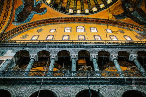 From below of aged stone columns and arched windows under ornamental dome in Hagia Sophia Mosque in Turkey