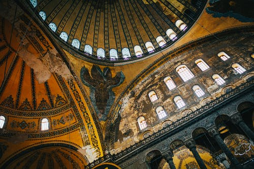 From below of interior of aged historic Hagia Sophia with domed ceiling and ornamental walls placed in Istanbul in Turkey in daylight