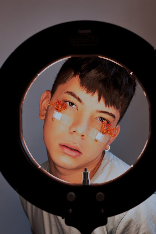 Young ethnic man with blossoming flowers and medical patches on cheeks looking at camera behind ring light