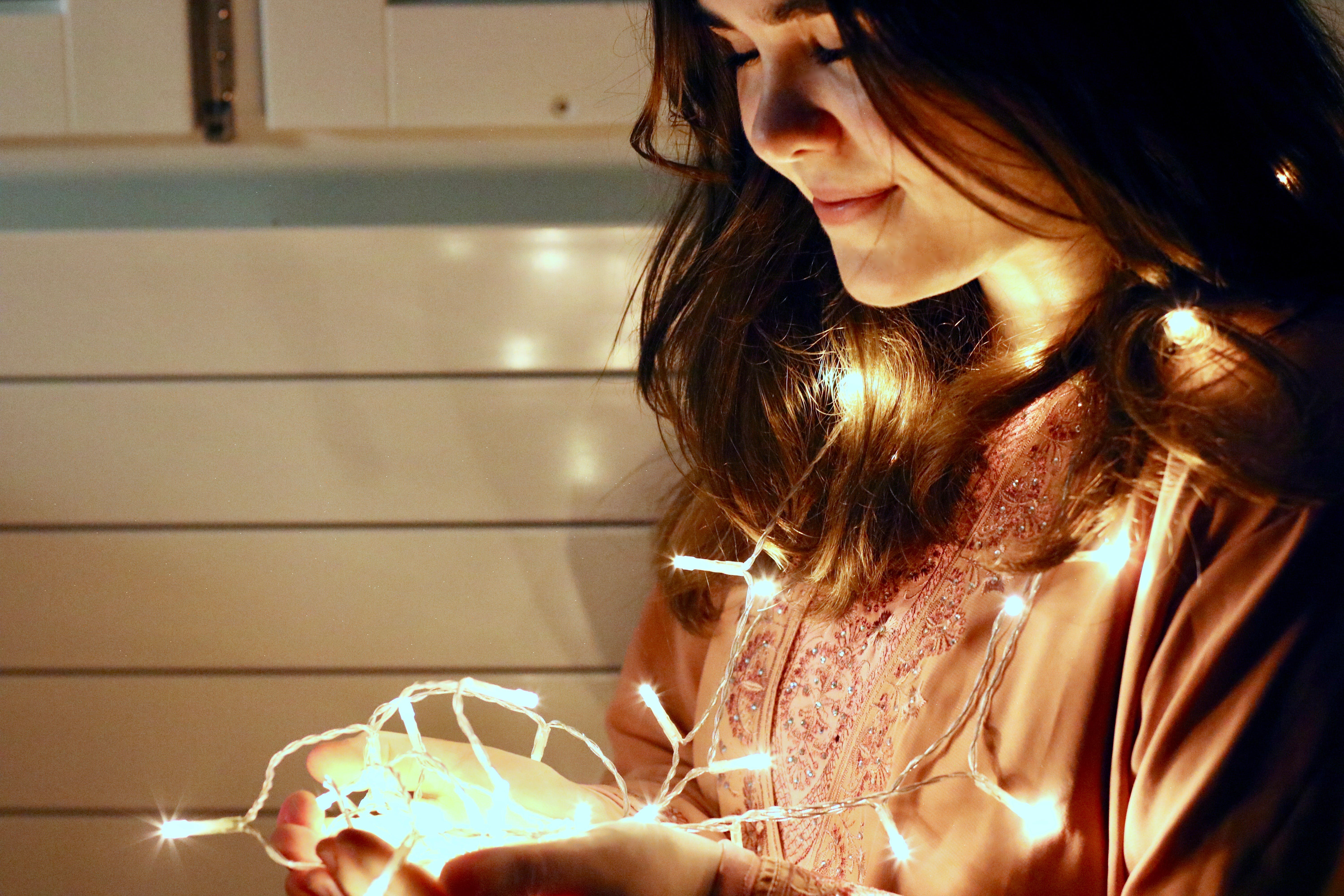 Woman Holding Lighted String Light