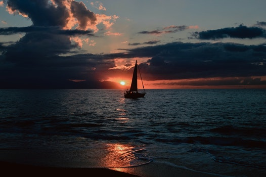 Silhouette of Sailboat on Body of Water during Sunset