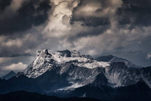 Snow Covered Mountain Peak Under Gray Clouds