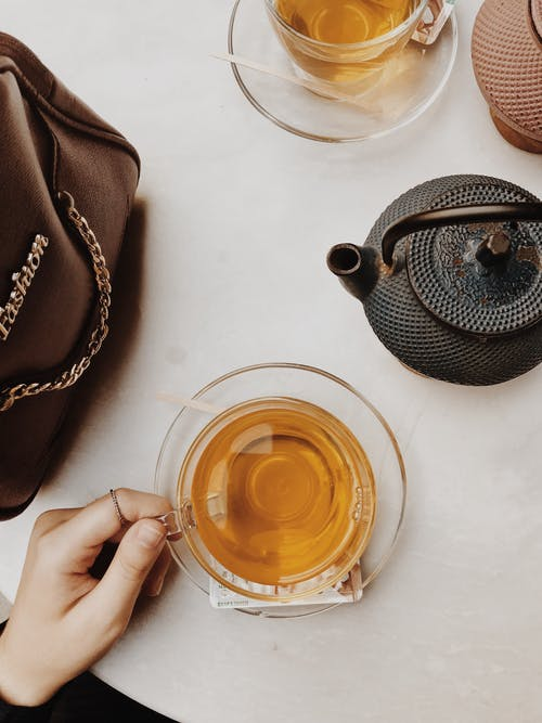 Woman with glass cup of herbal tea