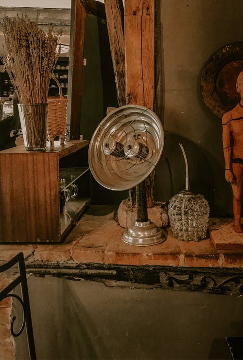Vintage metal heater placed on shelf in shop with antiques