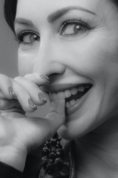 A Woman Biting Her Thumb and Smiling