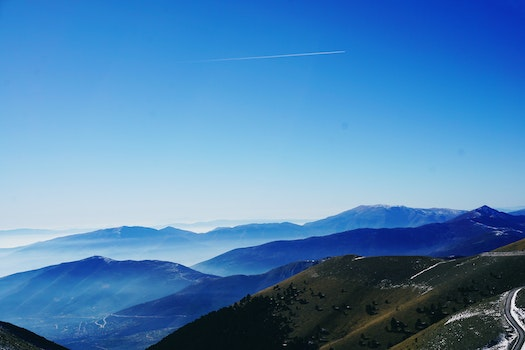 Green and Blue Fog Covered Mountains Under Blue Sky