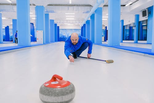 Concentrated sportsman with beard in blue uniform squatting down and looking at sliding stone with red handle during curling game on modern ice rink