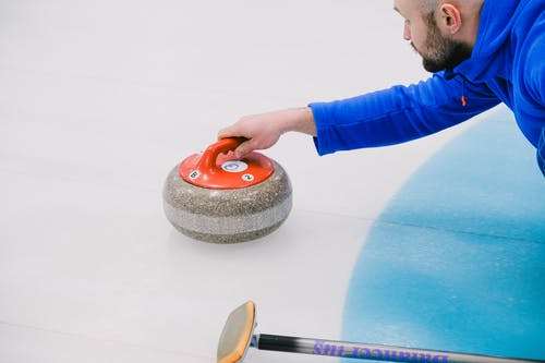 From above of crop concentrated player in uniform choosing trajectory of stone movement while playing curling on ice rink