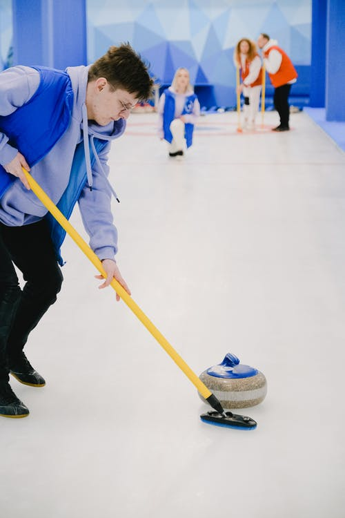 Young man sweeping ice with broom for moving stone