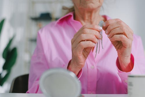 Close-Up Shot of an Elderly Woman in Pink Long Sleeves Holding a Jewelry