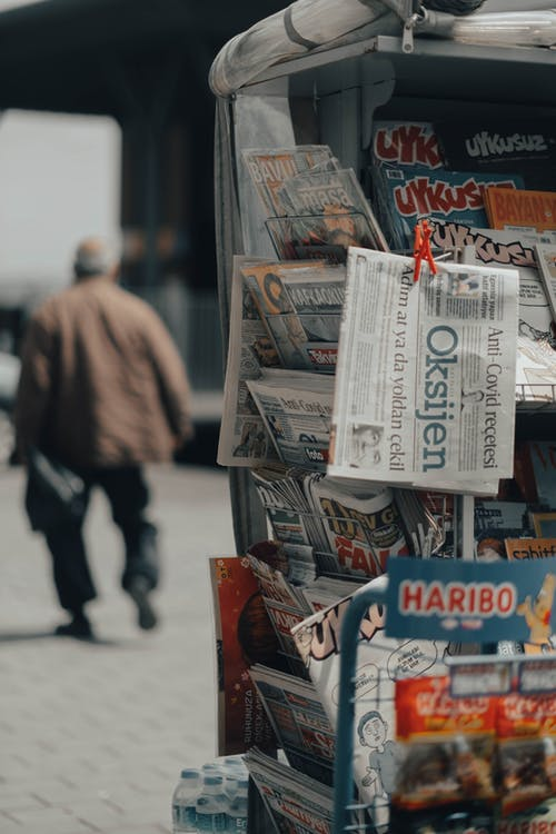 Newspapers and magazines in stand on city street near back view of faceless male walking on pavement in daylight