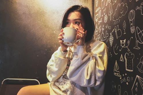 Woman Wearing White over Shirt Holding White Ceramic Mug Beside Black Printed Wall