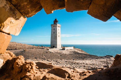 Through shabby stone hole of tall lighthouse located on shore near rippling sea against blue sky and horizon line in nature