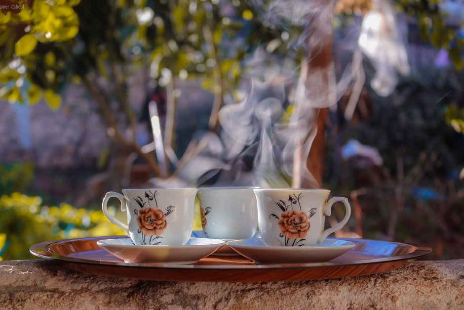 Shallow Focus Photo of Three White-brown-and-black Ceramic Floral Mugs on Saucers