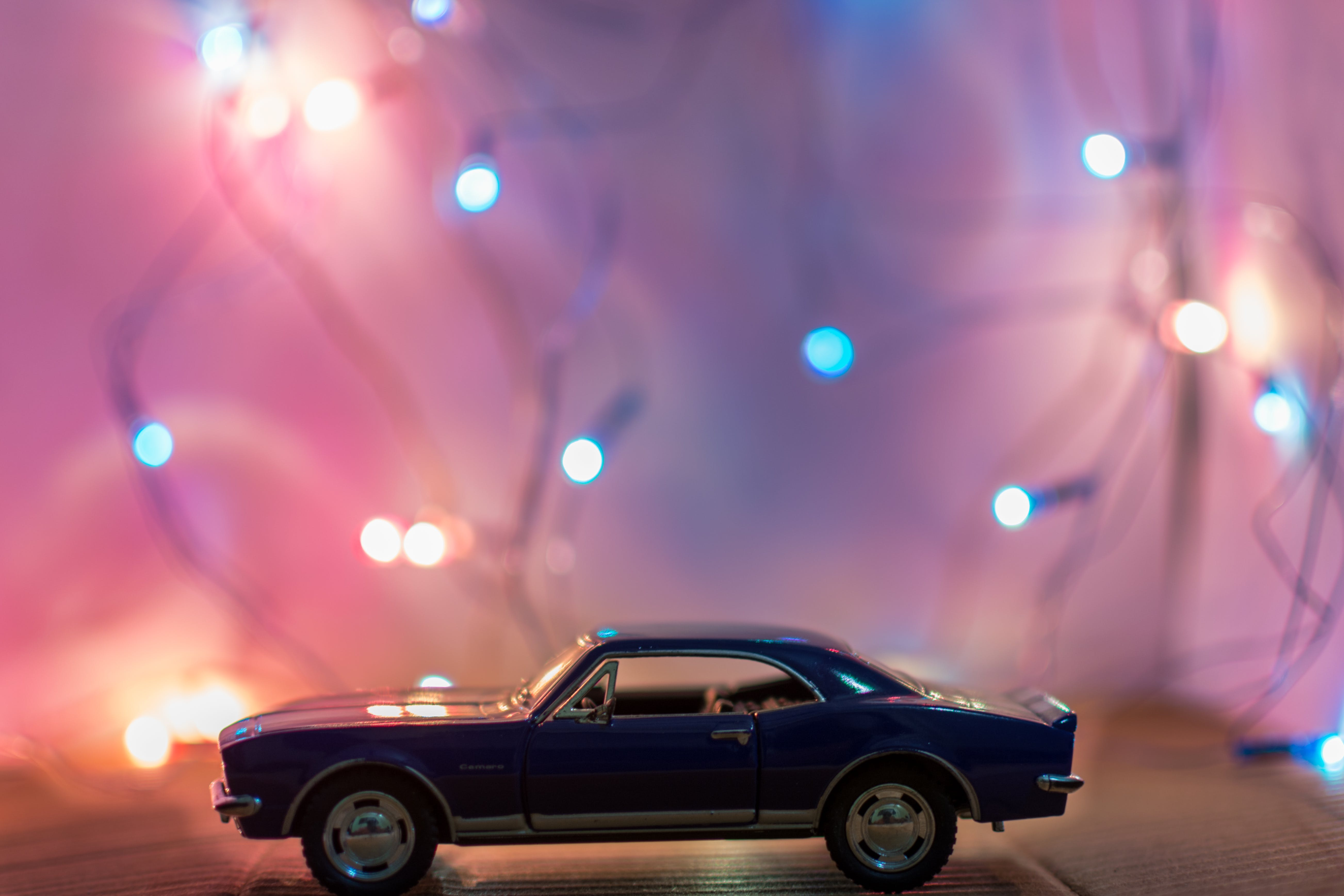 Selective Focus Photography of Classic Blue Coupe Die-cast Model in Front of String Lights on Table