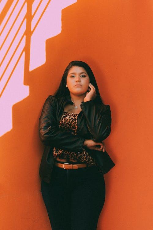 A Woman Standing Beside Orange Wall