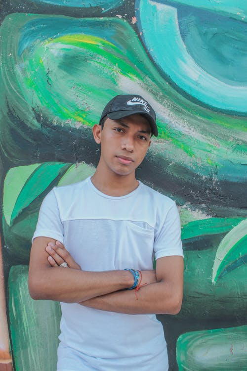 A Confident Man in White Shirt and Black Cap Standing next to a Colorful Wall
