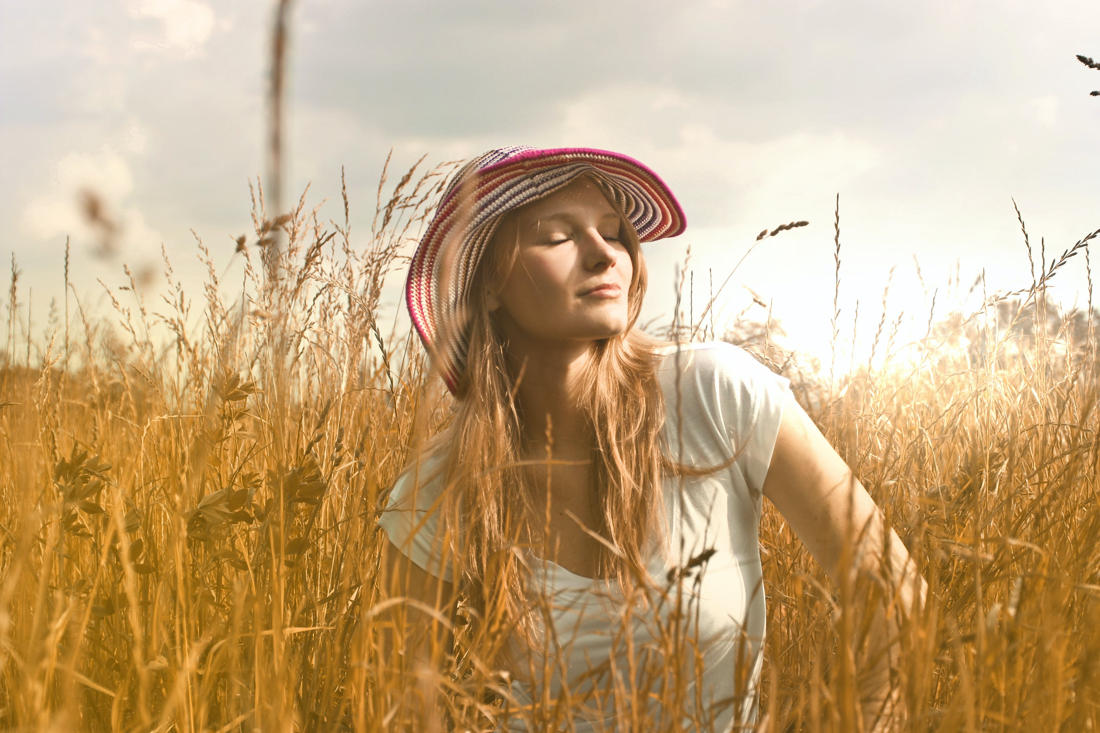 Woman Wearing White Top and Red and White Sunny Hat