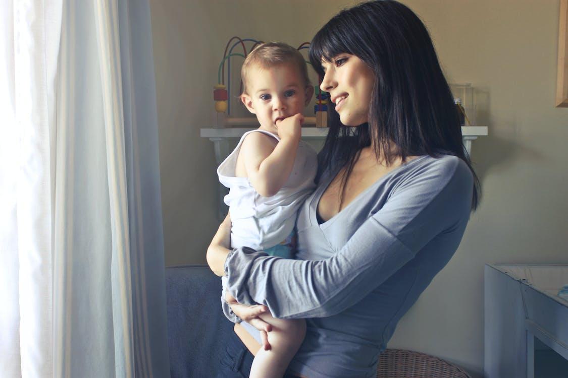 Mujer Con Baby Boy Vistiendo Tank Top Blanco Delante De La Cortina Blanca Dentro De La Habitación