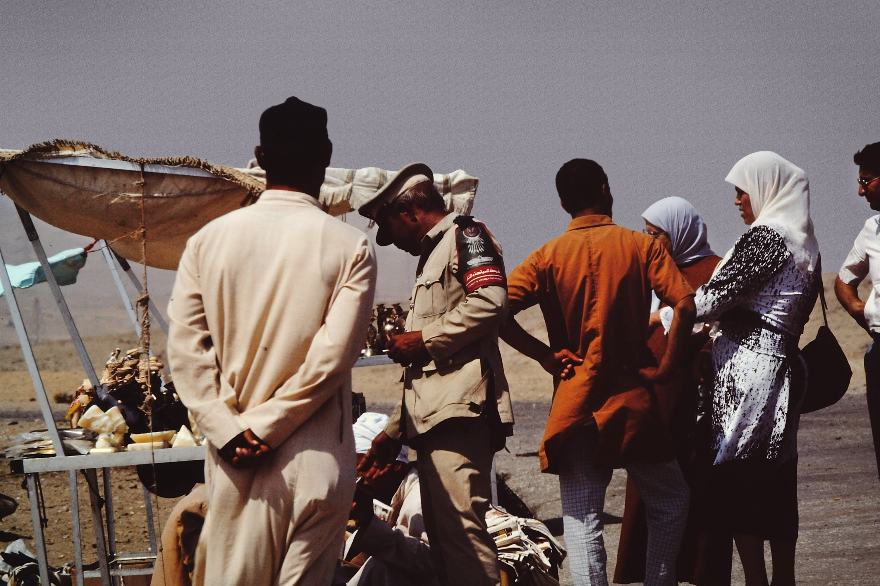 Group of People on Desert Beside Brown Tent