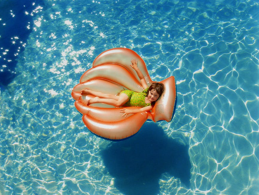 Girl Wearing Green Wet Suit Riding Inflatable Orange Life Buoy on Top of Body of Water