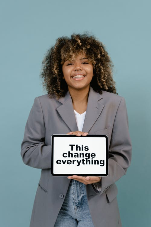 Woman in Gray Blazer Holding White Board
