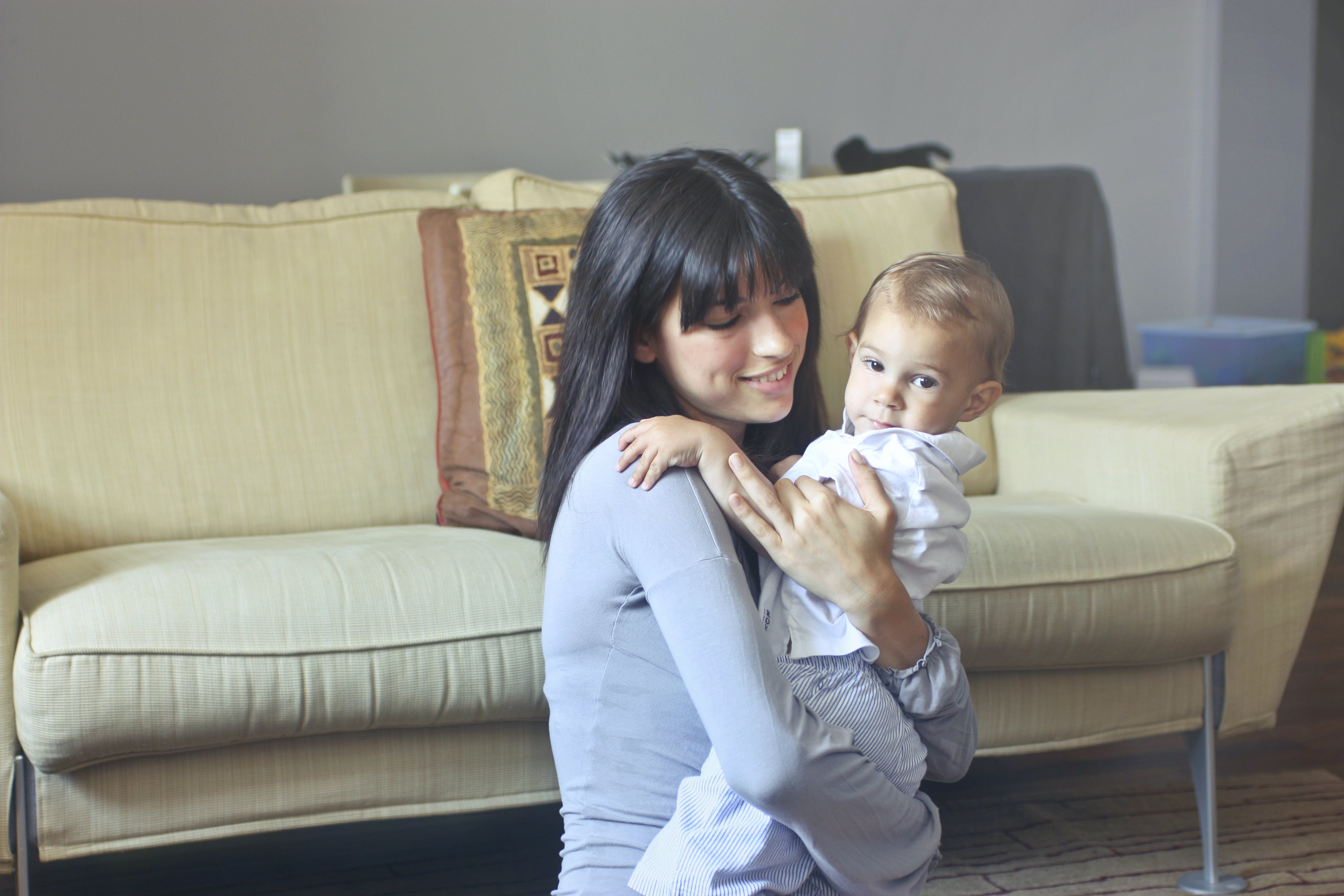 Woman in Gray Sweater Carrying Toddler in White Button-up Shirt