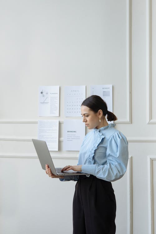Woman in Blue Dress Shirt and Black Skirt Holding White Laptop Computer