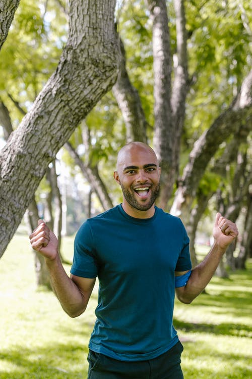 Man in Blue Crew Neck T-shirt Standing Beside Tree